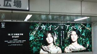 新宿駅東口のカインとアベルの大きなポスターのあるところが限定缶バッチ入手場所